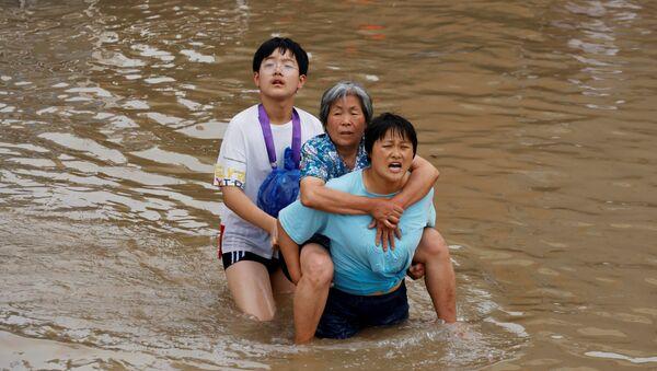 Женщина несет пожилую женщину  через паводковые воды после проливного дождя в Чжэнчжоу, провинция Хэнань, Китай - Sputnik Армения