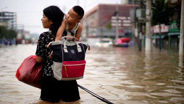 Женщина с ребенком и вещами пробирается через паводковые воды после проливного дождя в Чжэнчжоу, провинция Хэнань, Китай - Sputnik Армения