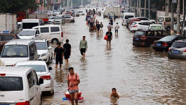 Люди переходят паводковые воды после проливных дождей в Чжэнчжоу, провинция Хэнань, Китай - Sputnik Армения