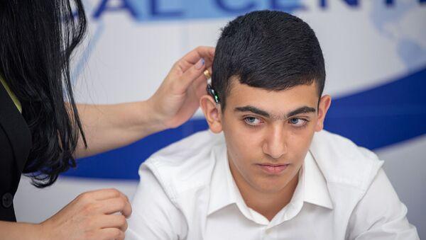 Один из прооперированных профессором Акирой Исиямой детей со слуховым аппаратом - Sputnik Արմենիա