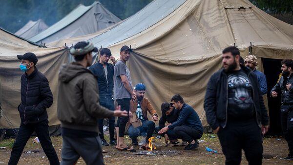 Мигранты готовят еду в недавно построенном лагере беженцев на военном полигоне Руднинкай (6 августа 2021). Литва - Sputnik Армения