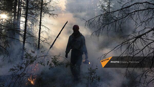 Сотрудник ФБУ Авиалесоохрана тушит лесной пожар в районе Хангаласский улус (9 августа 2021). Якутия - Sputnik Армения