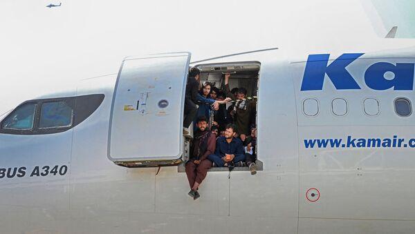 Афганцы сидят в дверях самолета в аэропорту Кабула  - Sputnik Армения