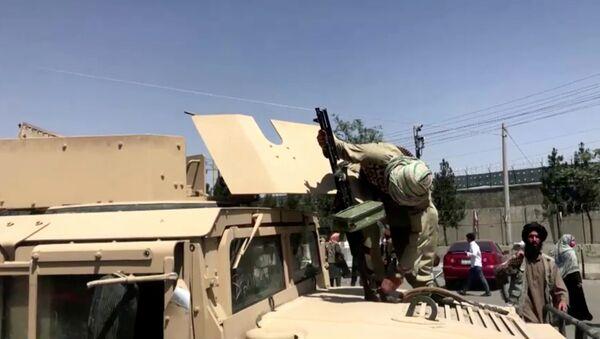 Боевик Талибана* с ружьем на бронетранспортере у аэропорта Кабула - Sputnik Армения