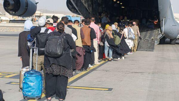 Афганские беженцы во время посадки на самолет C-17 Globemaster III ВВС США в международном аэропорту имени Хамида Карзая в Кабуле - Sputnik Армения