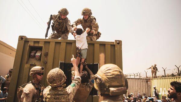 Британские и американские солдаты с детьми во время эвакуации в аэропорту Кабула  - Sputnik Արմենիա