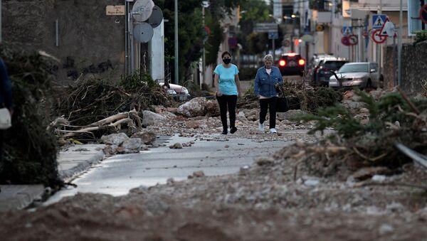 Женщины идут по улице, перекрытой упавшими деревьями и камнями после наводнения, вызванного проливными дождями в Альканаре (2 сентября 2021). Испания - Sputnik Армения