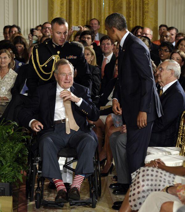 ԱՄՆ նախկին նախագահ Ջորջ Բուշը Սպիտակ տան արևելյան դահլիճում (հուլիսի 15, 2013), նստած է նախագահ Բարաք Օբամայի կողքին, Սպիտակ տան «Daily Point Of Light Award» -ի 5000-րդ մրցանակի հանձնման ժամանակ  - Sputnik Արմենիա