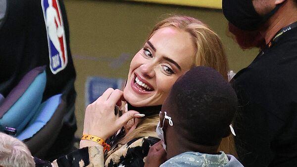 Певица Адель улыбается Ричу Полу во время второй половины Пятого матча Финала НБА между Милуоки Бакс и Финикс Санс (17 июля 2021). Финикс - Sputnik Армения