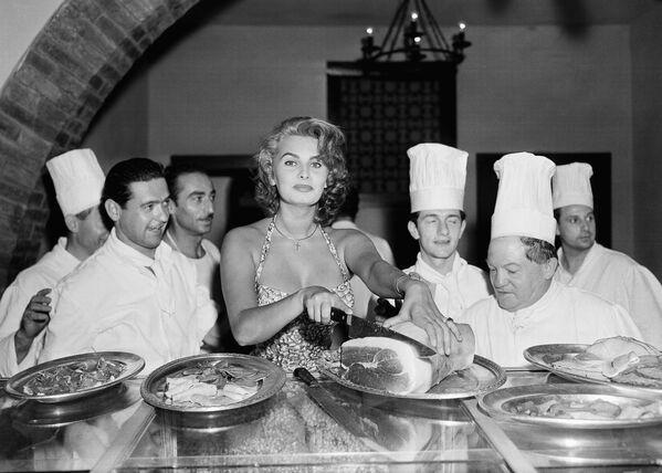 Софи Лорен – прекрасная хозяйка и автор книги рецептов. На этом фото она выскользнула с большой вечеринки в отеле Эксельсиор в Венеции 25 августа 1955 года, чтобы нарезать ветчину на тонкие пластинки. Ее поклонники-повара в восторге. - Sputnik Армения