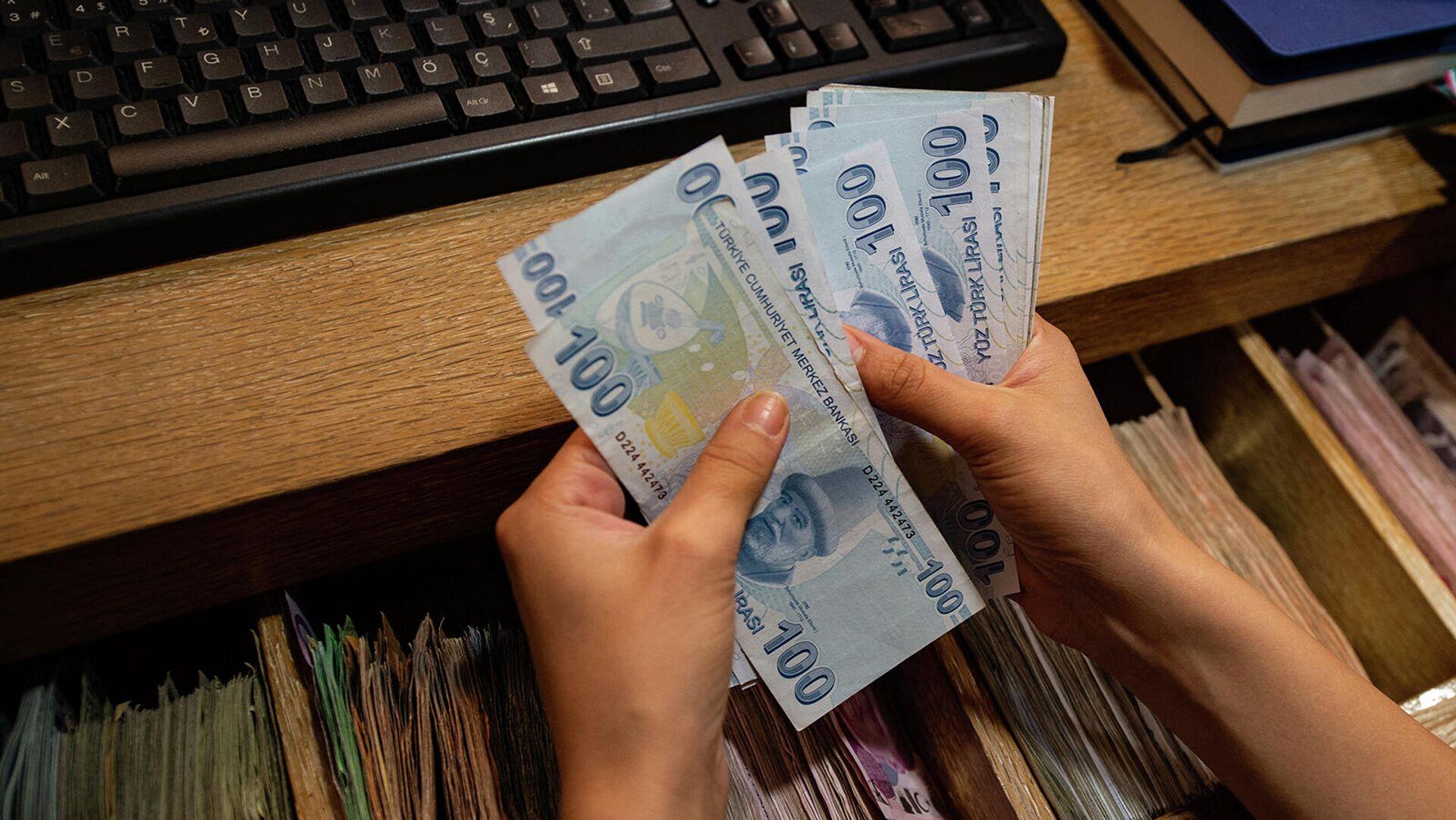 Сотрудник обменного пункта пересчитывает банкноты турецких лир - Sputnik Армения, 1920, 23.09.2021