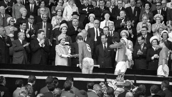 Королева Англии Елизавета II вручает приз VIII первенства мира по футболу Кубок Золотая богиня капитану английской сборной Роберту Муру - Sputnik Армения