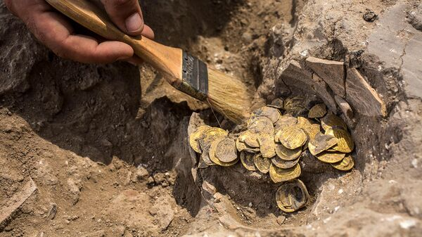 Археолог очищает обнаруженные на месте раскопок золотые монеты (18 августа 2020). Израиль - Sputnik Армения