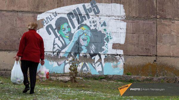 Пожилая жительница села Драхтик Гегаркуникской области проходит мимо граффити - Sputnik Армения