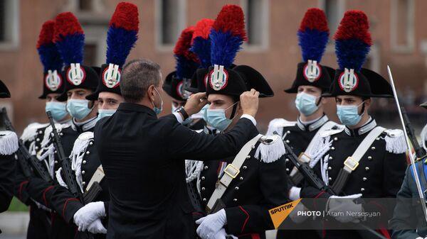 Сотрудник протокольной службы президента Италили приводит в порядок форму одного из офицеров почетного караула перед началом церемонии у Алтаря отечества на площади Венеции - Sputnik Армения