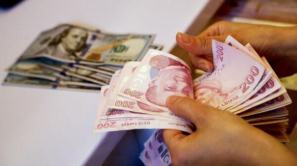 Сотрудник пункта обмена валют пересчитывает банкноты в турецких лирах (27 сентября 2021). Анкарa - Sputnik Армения