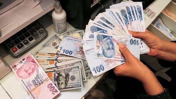 Сотрудник обменного пункта в Анкаре держит турецкие лиры. - Sputnik Армения