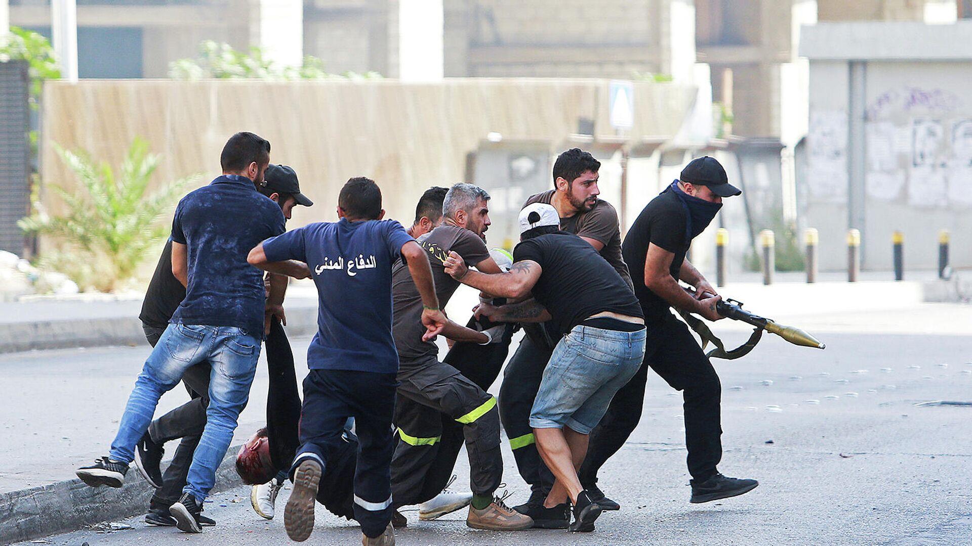 Люди эвакуируют пострадавшего после перестрелки (14 октября 2021). Бейрут - Sputnik Армения, 1920, 14.10.2021