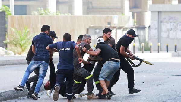Люди эвакуируют пострадавшего после перестрелки (14 октября 2021). Бейрут - Sputnik Армения