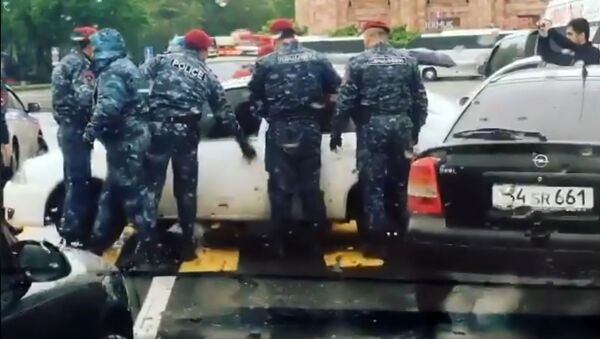 Сотрудники полиции пытаются открыть автомобили, перекрывшие улицы - Sputnik Армения