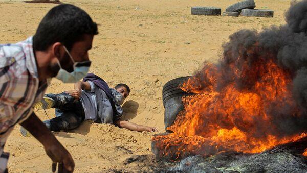 Палестинские протестующие сжигают шины во время столкновений с израильской армией вблизи границы с Израилем, к востоку от Рафаха в южной части сектора Газа в пятницу, 13 апреля 2018 года. - Sputnik Армения