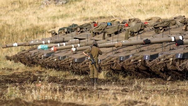 Израильский солдат рядом с танками Merkava Mark IV в районе развертывания вблизи сирийской границы (10 мая 2018). Голанские высоты - Sputnik Армения