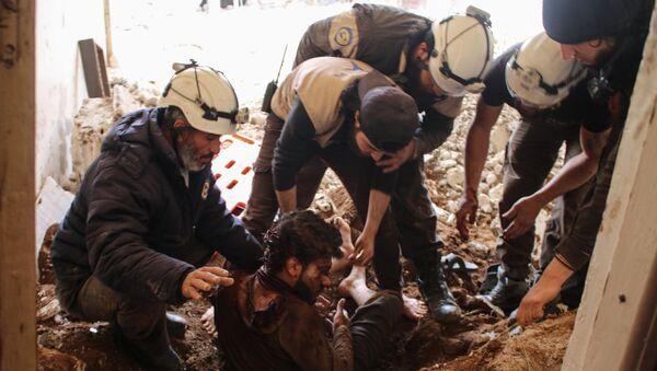 Члены сирийских добровольцев гражданской обороны, также известных как белые каски, извлекают жертву из обломков его дома (8 апреля 2017). Дараа, Сирия - Sputnik Армения