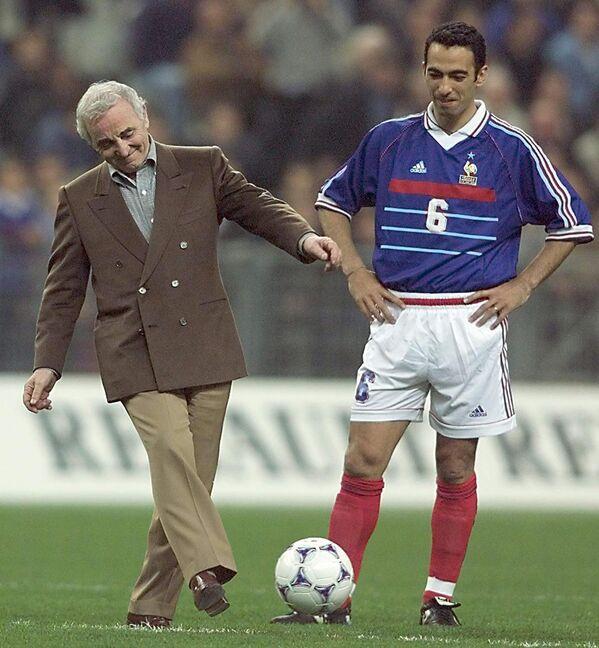 Շառլ Ազնավուրը և Ֆրանսիայի ֆուտբոլի հավաքականի հարձակվող Յուրի Ջորկայեֆի հետ Դե Ֆրանս մարզադաշտում՝ Ֆրանսիա-Հայաստան խաղից առաջ. 31-ը մարտի 1999 թ., Սեն-Դենի, Ֆրանսիա - Sputnik Արմենիա