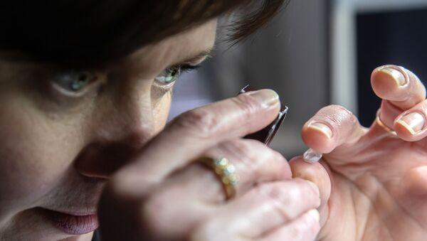 Сотрудница производит оценку бриллианта в цехе технического контроля и оценки ООО Бриллианты Алроса в Москве - Sputnik Армения