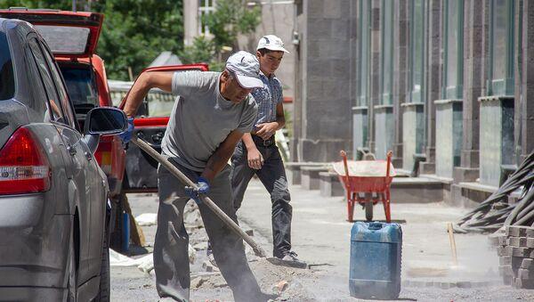Рабочий за укладкой дорожной плитки на улице Арама (9 июня 2019). Еревaн - Sputnik Армения