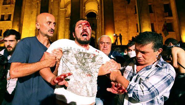 Демонстранты помогают раненому во время акции протеста против визита российского депутата Грузию (21 июня 2019). Тбилиси - Sputnik Армения
