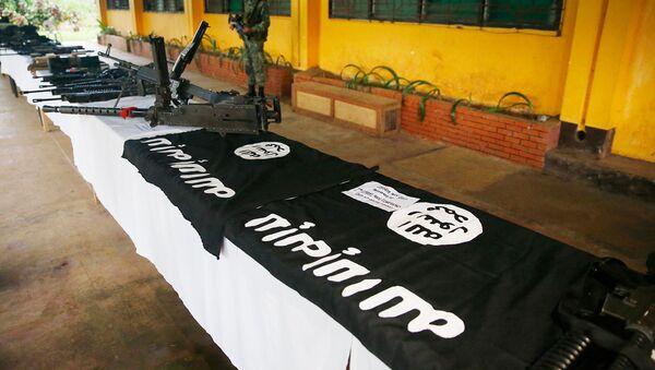 Филиппинский морской пехотинец охраняет показ мощного огнестрельного оружия, боеприпасов, униформы и черных флагов в стиле ISIS, которые были восстановлены от мусульманских боевиков (30 мая 2017). Марави, Филиппины - Sputnik Արմենիա