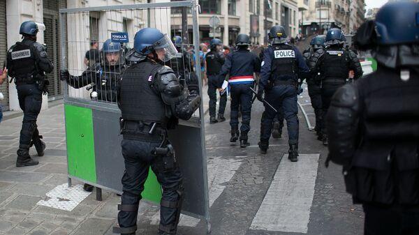 Сотрудники полиции преследуют демонстрантов после парада в День взятия Бастилии (14 июля 2019). Париж - Sputnik Армения