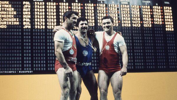 Победители летних Олимпийских игр в полулегком весе по тяжелой атлетике Дито Шанидзе (серебро СССР), Норайр Нурикян (золото Болгария) и Янош Бенедек (бронза Венгрия) на пьедестале почета после церемонии награждения (5 сентября 1972). Мюнхен  - Sputnik Армения