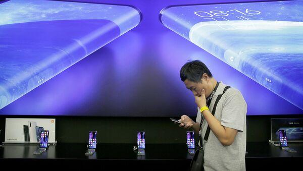 Журналист стоит рядом с плакатом Xiaomi Mi MIX Alpha на мероприятии по запуску продукта (24 сентября 2019). Пекин - Sputnik Արմենիա