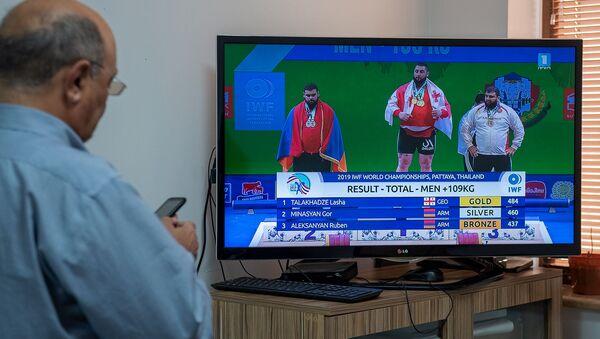 Сотрудник Sputnik Армения наблюдает за церемонией награждения чемпионата мира по тяжелой атлетике (27 сентября 2019). Еревaн - Sputnik Армения