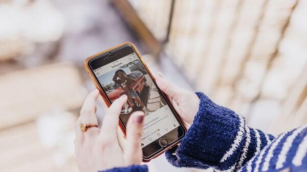 Девушка держит в руках смартфон с открытым приложением Instagram - Sputnik Արմենիա