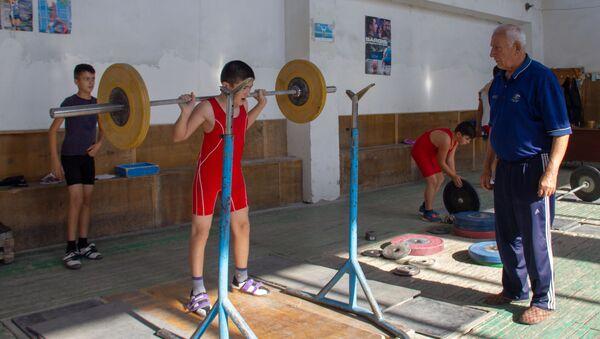 Заслуженный тренер по тяжелой атлетике Феликс Алиев наблюдает за тренировкой юных спортсменов в школе тяжелоатлетов села Гехакерт - Sputnik Армения