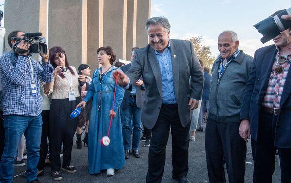 Гости и участники церемонии презентации парка Дружбы играют в волчка (17 октября 2019). Гюмри - Sputnik Армения