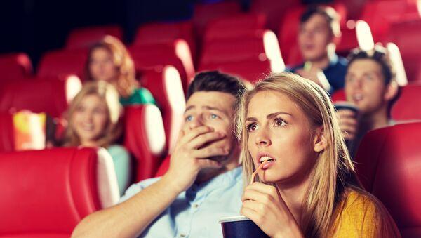 Девушка-блондинка с друзьями смотрит фильм ужасов в кинотеатре - Sputnik Армения