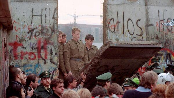 Восточногерманские пограничники видны через щель в Берлинской стене после того, как демонстранты снесли сегмент стены у Бранденбургских ворот (11 ноябрq 1989). Берлин - Sputnik Արմենիա