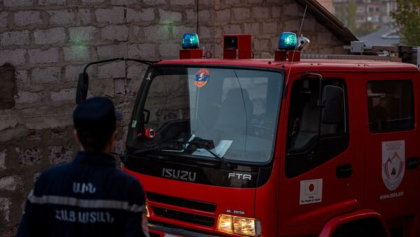 Сотрудник МЧС Армении у пожарного автомобиля - Sputnik Արմենիա