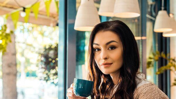 Красивая брюнетка с чашкой кофе в руке улыбается и смотрит в кадр - Sputnik Армения