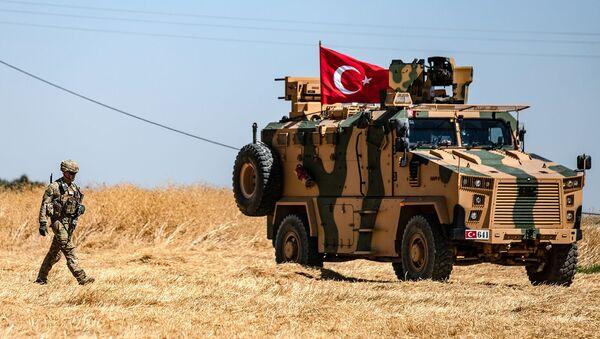 Американский солдат идет рядом с турецкой военной машиной во время совместного патрулирования с Турцией в сирийской деревне Аль-Хашиша на окраине города Таль-Абьяд вдоль границы с Турцией (8 сентября 2019). Сирия - Sputnik Արմենիա