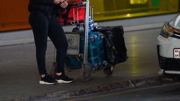 Пассажир с тележой для багажа в аэропорту Звартноц - Sputnik Армения