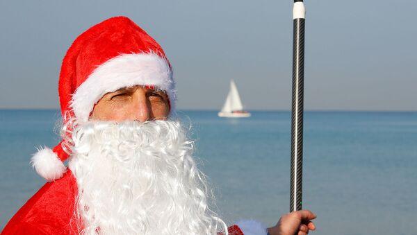 Израильский спасатель Арут Торосян в костюме Санта-Клауса позирует с веслом и доской на пляже (22 декабря 2019). Тель-Авив - Sputnik Армения