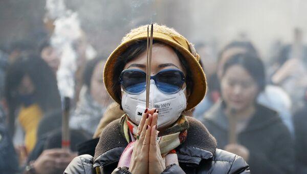 Женщина в маске и солнцезащитных очках во время молитвы в первый день Нового года в Пекине - Sputnik Արմենիա