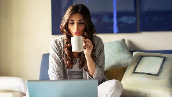 Девушка брюнетка с чашкой чая сидит на кровати и смотрит видео по ноутбуку - Sputnik Армения