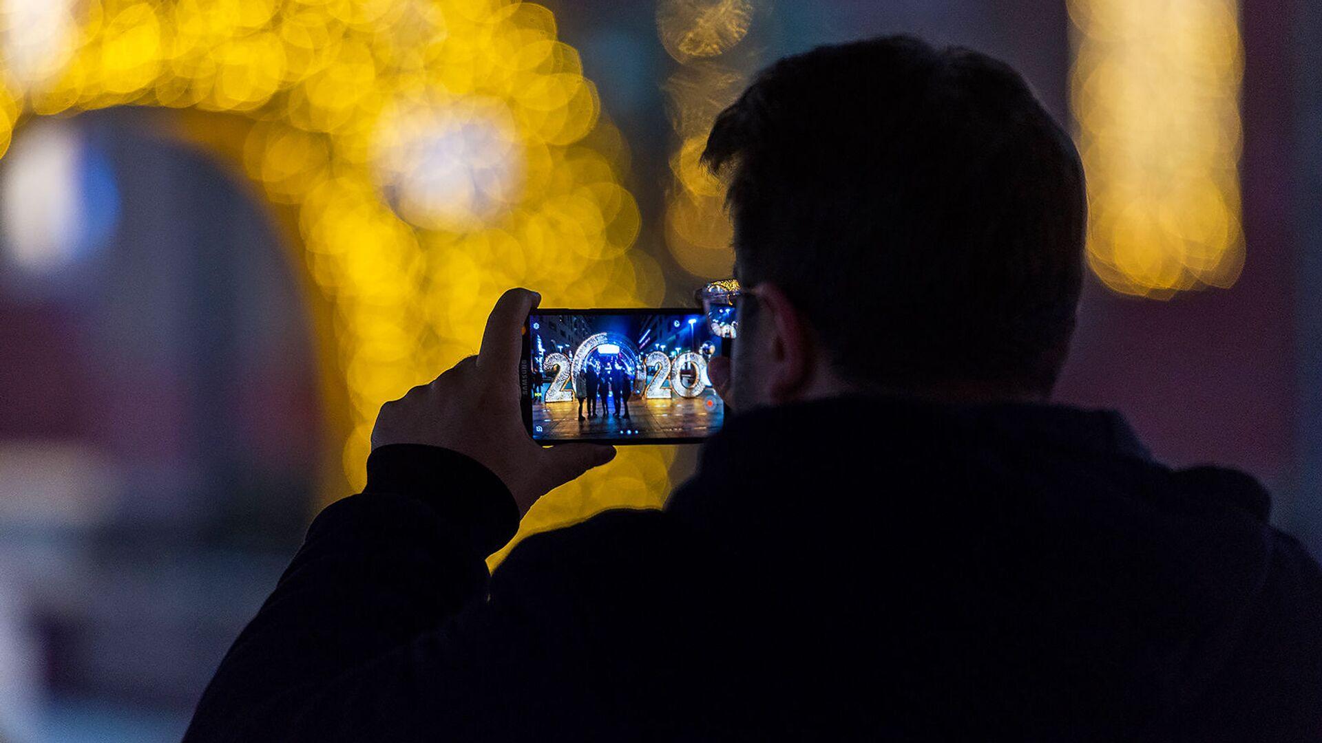 Турист фотографруют знакомых  у новогодней иллюминации на Северном проспекте - Sputnik Արմենիա, 1920, 15.04.2021