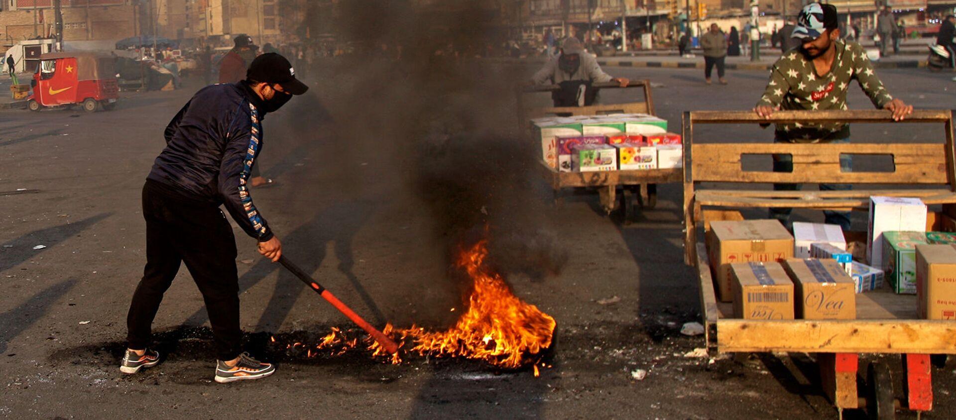 Протестующие устроили поджоги, чтобы закрыть улицы возле площади Тахрир во время демонстрации протеста против иранского ракетного удара (8 января 2020). Багдад - Sputnik Армения, 1920, 22.07.2021